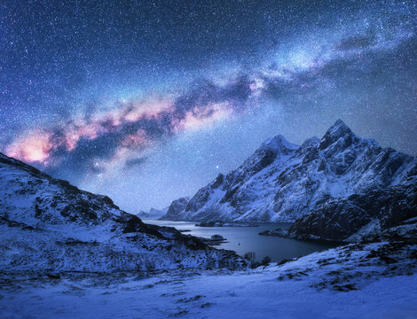 Bright Milky Way over snow covered mountains and sea bay at night in winter in Norway. Spectacular landscape with snowy rocks, starry sky, colorful milky way, beautiful fjord. Lofoten Islands. Space