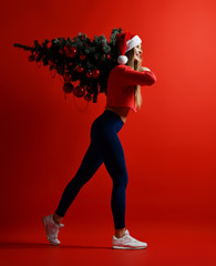 sexy Christmas fitness sport woman wearing santa hat holding xmas tree on her shoulders.