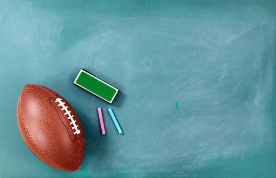 American football on cleaned chalkboard with writing supplies