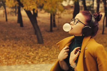 Cute young girl listening to music on headphones in autumn park. The girl has eggplant hair. She is wearing glasses and a mustard-colored coat. Woman bubbled up bubble gum
