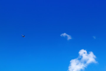 Airplane in the sky on a background of blue sky and white clouds. with blank copy space.