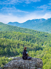 Girl sits in yoga pose at the edge of the cliff