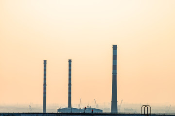 Factory chimneys under the yellow sky