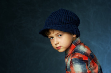 Portrait of a boy in a knitted hat on a dark background