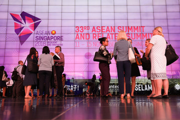 Delegates stand next to the ASEAN Summit signage at Suntec Convention Centre in Singapore
