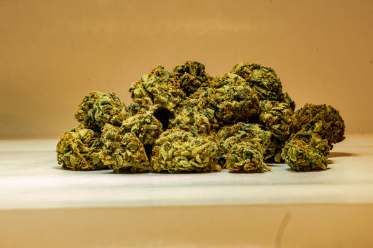 Close up of a pile of green marijuana buds isolated with a white background