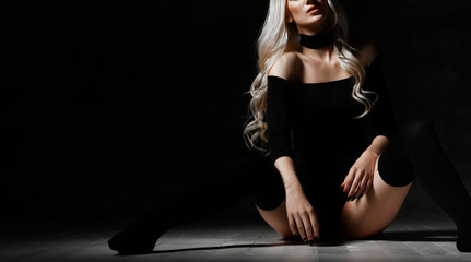 Young sexy blonde fashion woman sitting on floor in black body cloth and choker