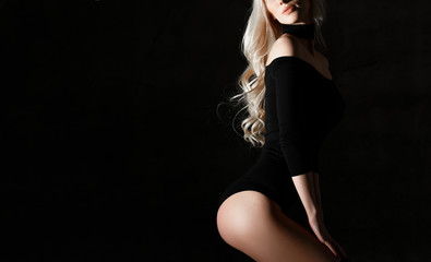 Young sexy blonde fashion woman lying on floor in black body cloth and choker