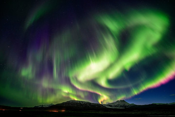 Strong Aurora over mountain at night in Iceland