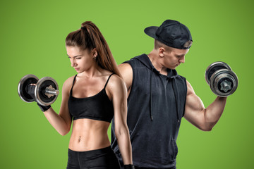 A young muscular woman and a fit man stand on a green background.