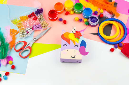 A box with a gift inside in the form of a rainbow unicorn.