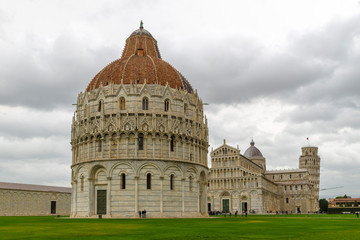 PISA, ITALY - OCTOBER 29, 2018: The Baptistery in the foreground, the Duomo in the center, and the leaning tower in the background on the right