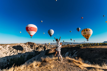 Couple in love among balloons. A guy proposes to a girl. Couple in love in Cappadocia. Couple in Turkey. Honeymoon in the mountains. Man and woman traveling. Flying on balloons. Wedding. Journey. Love Wall mural