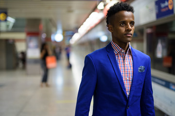 Young handsome African businessman at the subway train station i