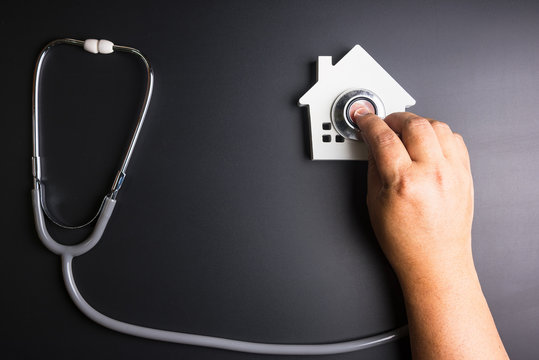 House model with stethoscope isolated on black background.Indicates the health of the house.