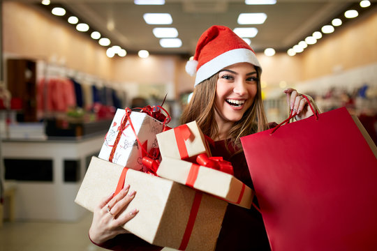 Happy girl shopping gifts in mall on christmas sale. New year holidays shopping idea concept. Smiling woman with colorful paper presents bags and gift boxes wearing christmas hat in store or shop.