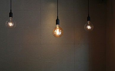 Hanging Lamp decor against gray tile wall background.