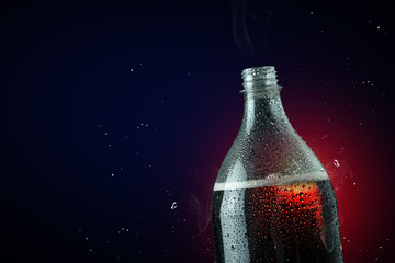 Soft drink bottle with ice splash on dark background.