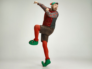 friendly man dressed like a funny gnome posing on an isolated gray background Wall mural