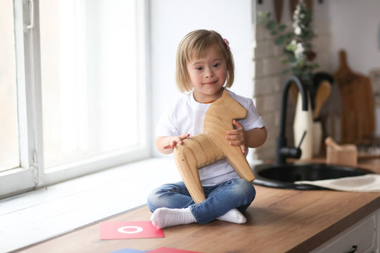 Toddler with Down syndrome plays with wooden horse