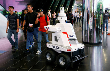 A police surveillance robot patrols the lobby of Suntec Convention Center during the ASEAN Summit in Singapore