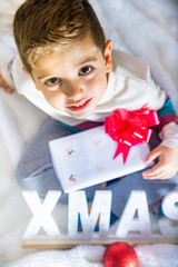 Littlr kid on Christmas day on the bed with a gift