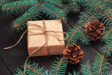 Christmas gift boxes and fir tree branch on wooden table.