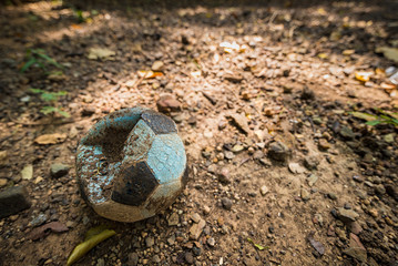 Old deflated soccer ball on the field.Thailand.
