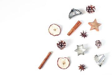 Christmas festive styled food composition, pattern. Pine cones, dried apple fruit, cinnamon, vintage cookie cutters and anise stars isolated on white wooden background. Flat lay, top view. Baking.