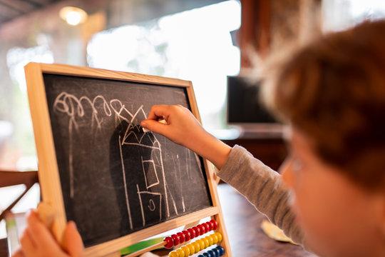 Bambina che disegna e scrive alla lavagna e si diverte