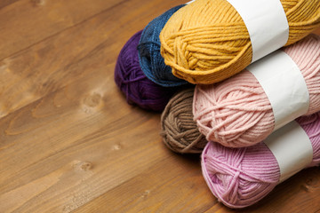 colorful wool yarn for knitting on wooden background