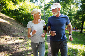 Mature couple jogging and running outdoors in city Wall mural
