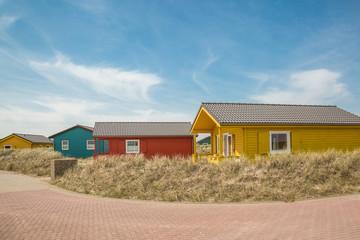 Farbenfrohe Holzhütten mit Strandgras