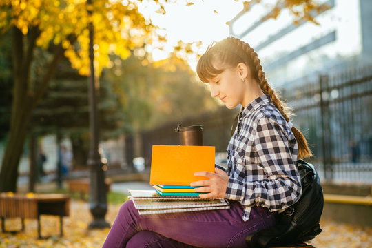 Happy 12 years old teen girl in eyeglasses with two braids reading workbooks in the autumn park after school.