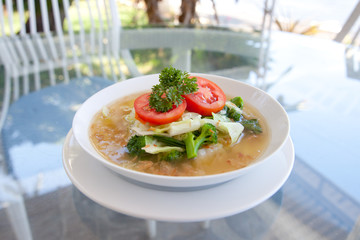 vegetable soup in a plate on a glass table