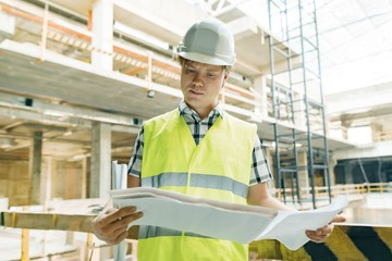 Portrait of male engineer at construction site. Builder looks at the plan of the construction site. Building, development, teamwork and people concept