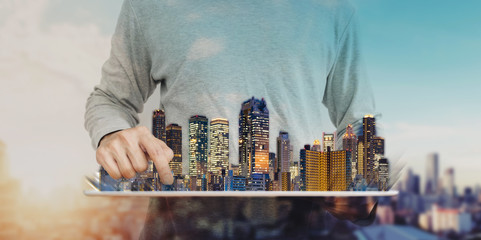 a man using digital tablet with modern buildings hologram. Real estate business and investment, building technology