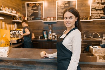 Portrait of young female small business owner - small modern coffee shop, confident woman standing at the counter with barista working in background making drinks