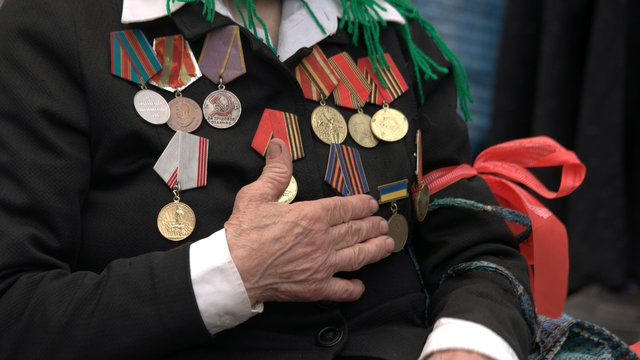 War veteran with hand over heart and awards. Orders and medals on female veteran chest. Celebration of Victory Day.