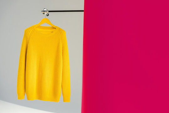 knitted yellow sweater on hanger on pink and grey background