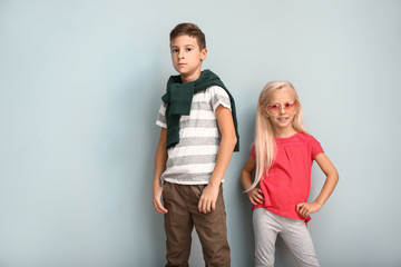 Cute boy and girl in fashionable clothes on color background