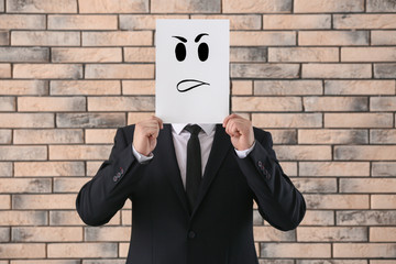 Businessman hiding face behind sheet of paper with drawn emoticon against brick wall