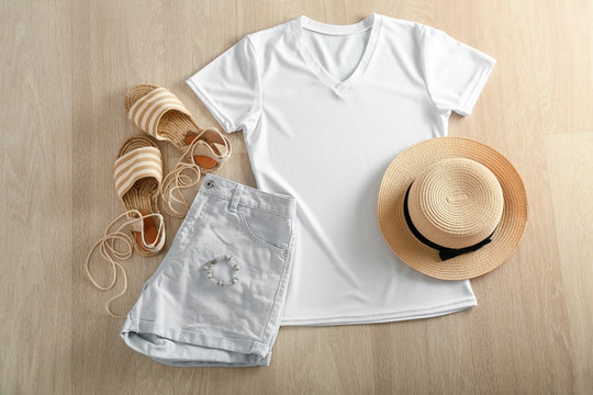 Composition with white t-shirt, shorts, hat and shoes on wooden background