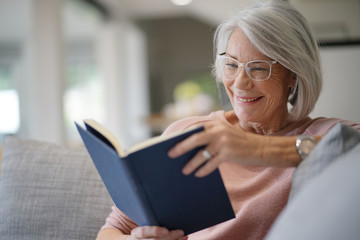 Senior woman reading on couch at home
