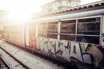 A train with closed doors waiting for passengers at the railway station. Street art and urban culture painted on the tube, Sunlight in background
