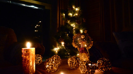 shiny, golden Christmas decorations with the candles xmas toys and the tree with garlands in background, evening