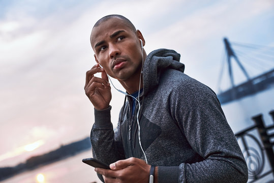 The young black athlete is listening to music after training in the city