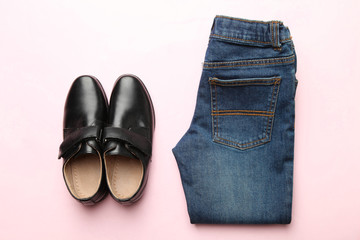 Black classic shoes and jeans on a pink background. Concept clothes. Top view.