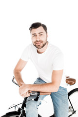 Handsome smiling young adult man riding bicycle isolated on white