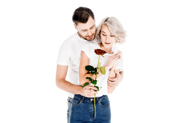 Beautiful couple with flower hugging while man giving to woman red flower isolated on white